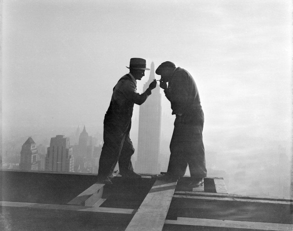 2 decembrie 1932, doi muncitori care lucrau la clădirea RCA își aprind țigările. În fundal, silueta Empire State Building, ce arată înălțimea la care se aflau cei doi. | Imagine originală, Credit: Bettmann Archive, Sursa: History Collection