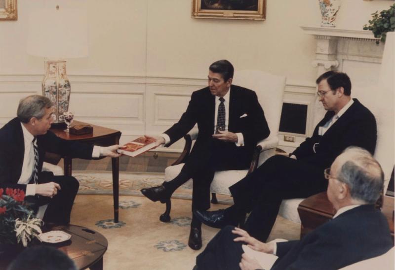 """În imagine, președintele Ronald Reagan în Biroul Oval, primind cartea """"Orizonturi Roșii"""" scrisă de Ion Mihai Pacepa după fuga din România"""